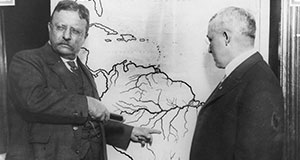 Pictured: President Roosevelt pointing at a map of South America towards the area explored during the Roosevelt-Rondon Scientific Expedition in Brazil.