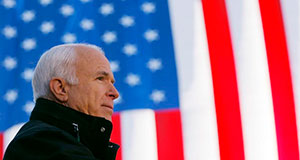 Pictured: Senator John McCain in front of American flag.