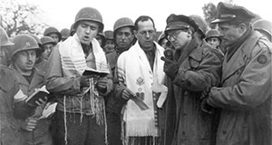 Pictured: Max Fuchs (left in prayer shawl) singing in Aachen, Germany during the first Jewish service to be held on German soil since the rise of Hitler, which was broadcast on NBC. Rabbi Chaplain Sidney Lefkowitz is next to him. Oct. 29, 1944.