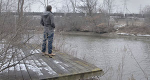 Pictured: At the Flint River during the 2016 crisis, What Lies Upstream director Cullen Hoback looks at the iconic water tower in the distance.